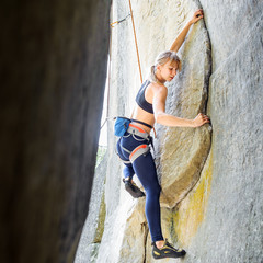 Sporty blonde female climber climbing steep stone wall in nature