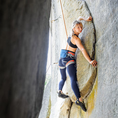 Blonde cute climber climbing with rope natural rock wall