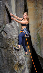 Young beautiful female climber climbing with rope on a steep roc