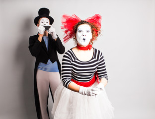 Funny couple of mimes taking a selfie photo on a mobile phone. Concept of  April Fools Day.