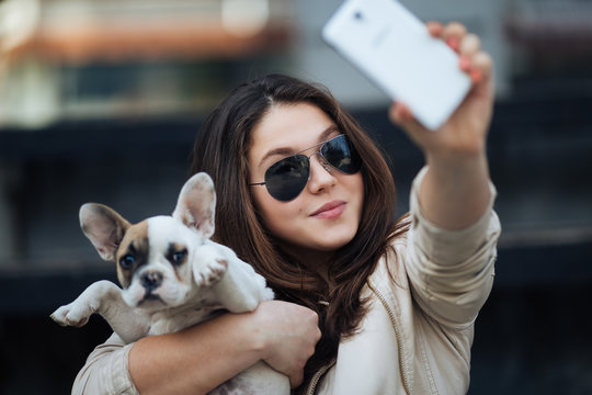 Beautiful young girl smiling and taking a selfie with her cute French bulldog puppy. Urban scene. Selective focus on girl.