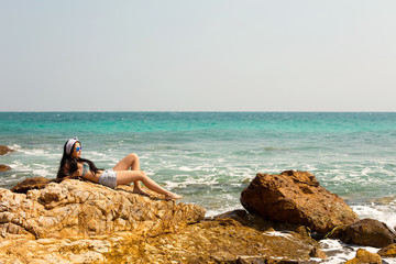 Young Girl on rock beach, looking on blue ocean and relaxin