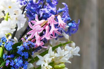 Frühlingsgruß - Ein bunter Frühlingsstrauß aus rosa, weißen und lila Hyazinthen und Vergißmeinnicht vor einer Holzwand