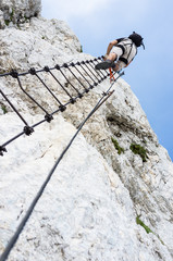ferrata - crawling man in mountains, climber with helmet and a backpack from the summit