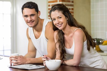 Young couple reading newspaper while having breakfast