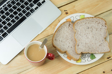 laptop, bread, and a red cup of coffee on a rustic wooden cafe t