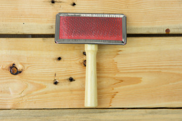 Grooming tools. Close up on brush on wooden background