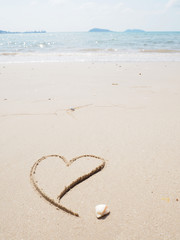 Heart-shape drawing on the sandy beach with sea background