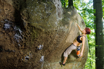 Young athletic female rock-climber on large boulder, hanging on one hand and holding hand in magnesium bag. Looking at the camera. Summer time