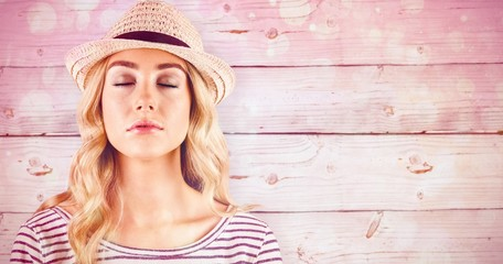 Composite image of gorgeous blonde hipster with straw hat