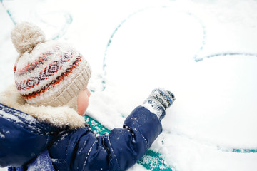 The boy draws heart on snow. Outdoor. Winter, love, friendship, concept.