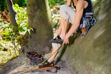 Foto op Aluminium Alpinisme Female climber sitting on a big rock and putting her climbing shoes on. Getting ready for climb. Climbing equipment. Outdoor summer day.