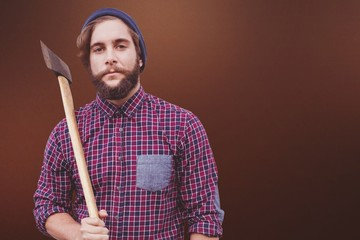Composite image of portrait of hipster holding axe