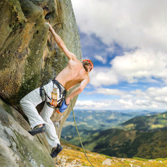 Muscular rock climber climbs with rope and garbines on overhanging cliff against blue sky and scenic mountain background. Hanging on one hand and holding hand in magnesium bag. Summer time.