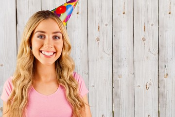 Composite image of portrait of a beautiful woman with party hat