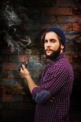 Composite image of side view of hipster holding smoking pipe