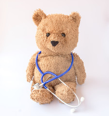 Blue stethoscope and teddy bear on white background