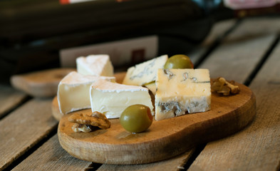 Camembert and blue cheese layes on the wooden board