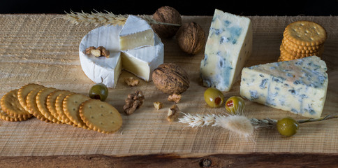 camembert and blue cheese with green olives and crackers on the wooden board as a perfect appetizer