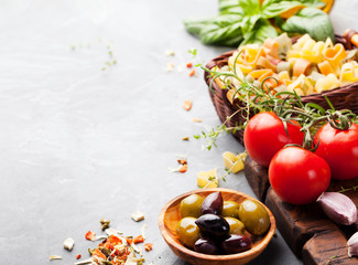 Italian food background with vine tomatoes, basil, spaghetti, olives Ingredients on stone table Copy space