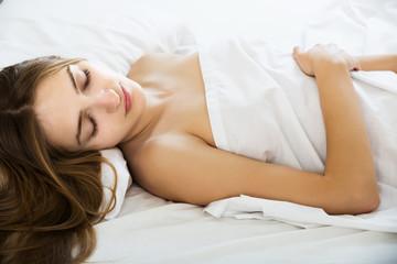 Brunette girl sleeping in bed