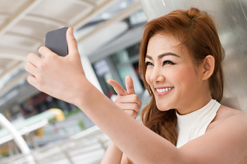 woman taking a selfie with her smartphone, pointing up to the ca