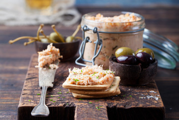 Smoked salmon and soft cheese spread, mousse, pate in a jar with crackers and capers on a wooden background