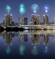 Fireworks celebrating over Tokyo cityscape with mirror reflectio