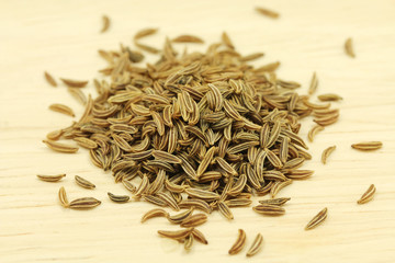 a handful of cumin seeds on wooden texture