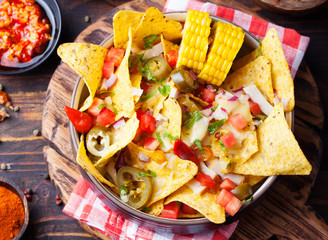 Nachos with melted cheese sauce, salsa and corn cobs in bowl on wooden background Top view