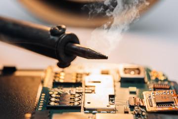 Repair smartphone. Male solder parts smartphone. Close-up.