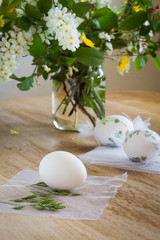 Egg being wrapped with herbs before painting