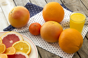 Orange juice and citrus slices on wooden table