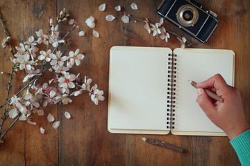 woman writing on blank notebook next to spring white cherry blossoms tree on vintage wooden table.
