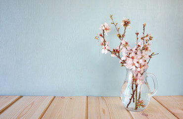 spring bouquet of flowers on the wooden table with mint background. vintage filtered image