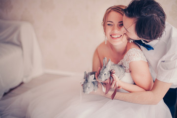 closeup photo ofbeautiful smiling bride with rabbits in her hands kissed by the groom in warm colors
