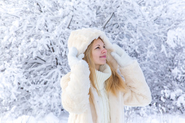 Young beautiful woman walking in park and breathing fresh winter air and delight about snow