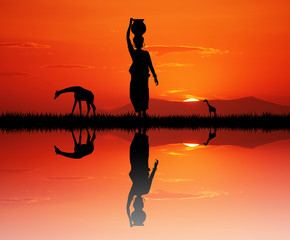 African woman carrying water at sunset