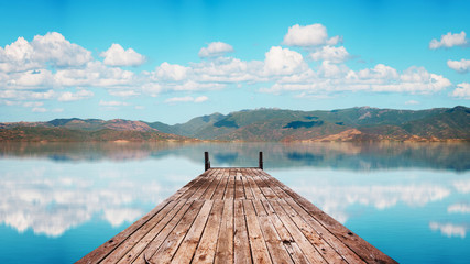 Perspective view of a wooden pier in a completely calm lake with reflections of the sky Wall mural