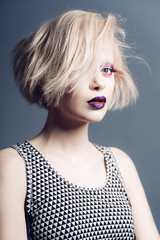 Portrait of a beautiful blonde young girl in a studio with a red makeup, beauty concept