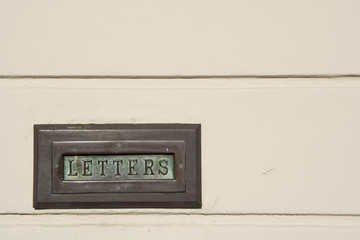 Verdigris Brass Letter Box in an off white wall Landscape