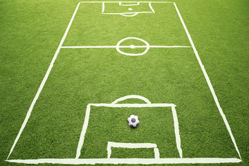 Beautiful sketched soccer field with soccer ball on sunny grass background.