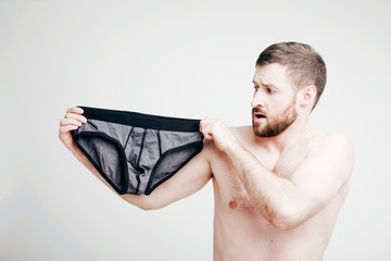 Young attractive bearded naked man holding briefs
