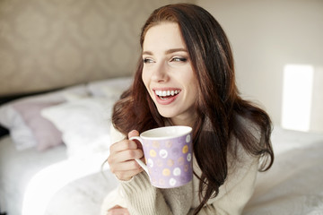 woman with a cup of coffee in the morning in the bedroom