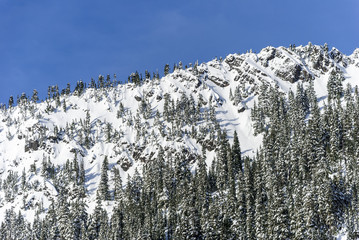 Blue Sky Above Snowy Cliffs on Mountain Ridge