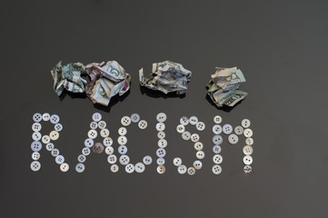 Racism spelled out with buttons.  Crumpled up money on top.