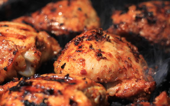 Delicious and juicy seasoned chicken thighs being cooked on a charcoal barbeque grill
