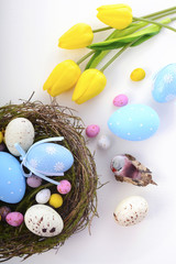 Easter eggs in nest on white wood table.