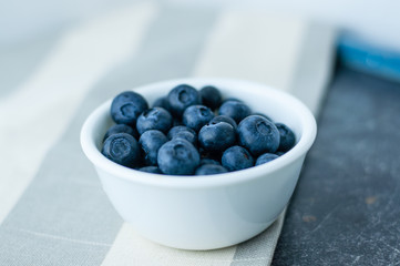 Small white bowl of blueberries linen tablecloth close up, side view