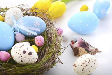 Easter eggs in nest on white wood table.